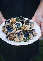 A woman holds a plate of Grilled Clams