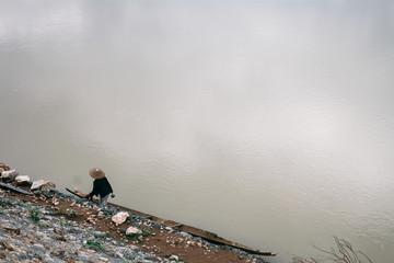 A woman walks along the edge of the Mekong River