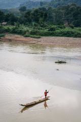 A man crossing the Mekong River on his wooden boat
