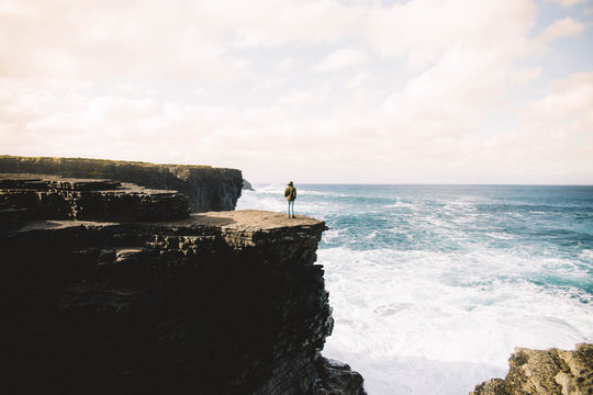 Person standing on climb looking at seascape