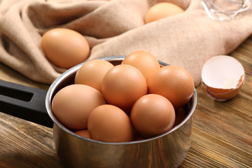 Raw eggs in saucepan on wooden table