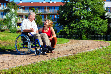 man on wheelchair with young woman