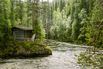 A beautiful small wooden house on a bank of a river in Finland