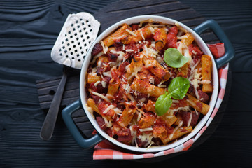 Casserole with ziti over black wooden background, above view