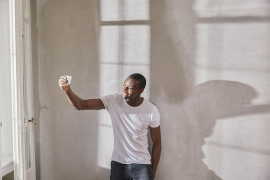 Smiling young man taking selfie with cell phone