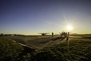 Flugzeuge auf einem Rollfeld im Sonnenuntergang