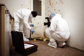 Team of criminologist technicians working on shotgun evidence on crime scene