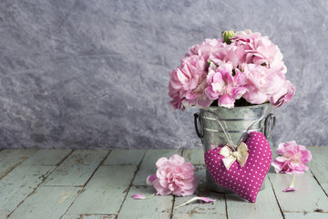 Pink heart and carnation flowers in zinc bucket on old wood