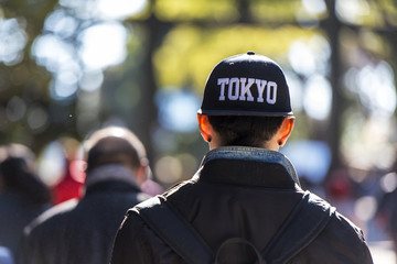 A young man dressed in fashion cap going in a park in Tokyo Japan
