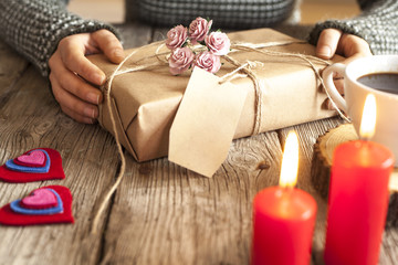 Woman hands holding gift on wooden background