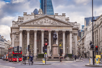 London, England - Iconic red double decker bus and the Royal Exchange building