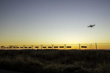 Flugzeug fliegt über den Zaun eines Flugplatzgeländes im winterlichen Sonnenuntergang