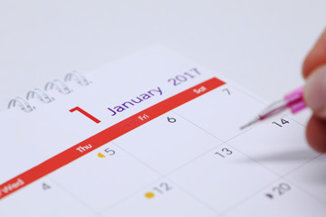 hand writing work schedule on desktop calendar of 1 january 2017