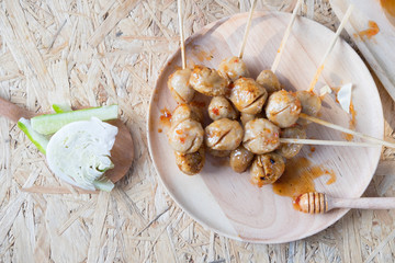 Meatball topped with spicy sauce.