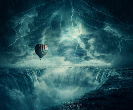 StormFall Inspirational imaginary view, scary landscape as a hot air balloon fly over the chasm of a foggy waterfall below a dark stormy sky.