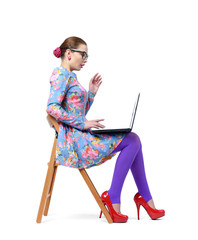 Fashionable young girl in glasses sitting on a chair with laptop isolated on white background