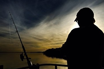Silhouette of a Lady Fishing at Sunset