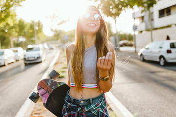 Smiling young woman with skateboard standing on the street