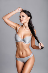 Perfect body young woman on a gray background