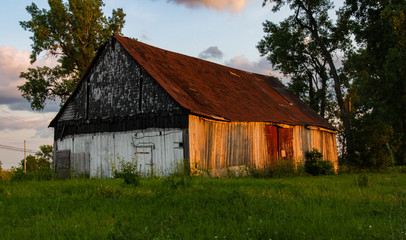 Old barn with trees at sunset