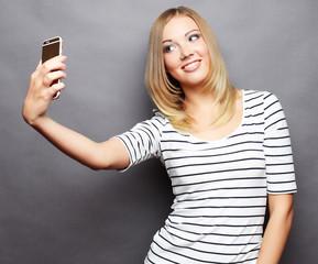 stylish woman making selfie photo on smartphone over grey  backg