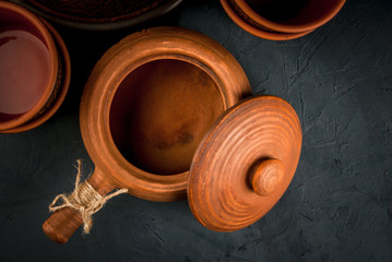 Clay rustic dishes on a stone  table: pot  (pan), plates and gravy boat, top view copy space