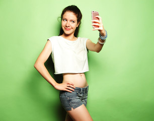 Charming woman making selfie photo on smartphone over green back