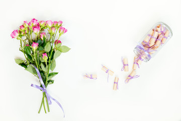 Dreams written on a pink rolled paper in a glass jar and fresh pink little roses. Flat lay on white background, top view.