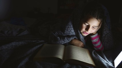 girl teen child book reading night with flashlight lying a under blanket