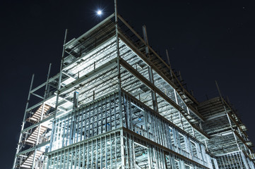 metal framed multi floor building under construction illuminated at night