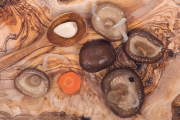 Shiitake marinated mushrooms with wooden spoon on olive wood cutting board