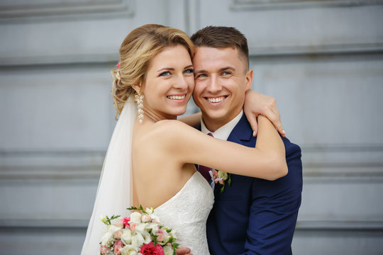 Wedding couple, portrait of happy bride and groom on background with copy space. Young and beautiful couple in love with smiling faces at their wedding day