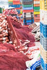 Africa,North Africa,Morocco, Rabat,Sale,red and white fishing nets stacked next to colorful plastic crates on dock, near mouth of the Bou Regreg river.
