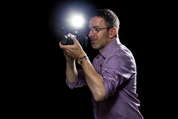Male paparazzi or editorial photographer journalist using a speedlight flash strobe in the dark