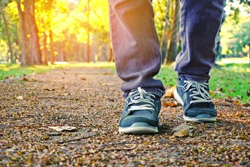man legs walking in a park with beautiful nature spring background