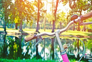 closeup vintage bicycle with blur background of nature green park and sunlight