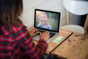 Young woman sat looking her son picture from laptop while relaxi