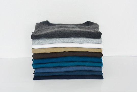 stack of t-shirt on white background, copy space