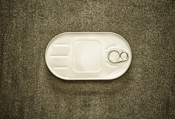 closed canned fish in a white oval box on a gray background, view from above