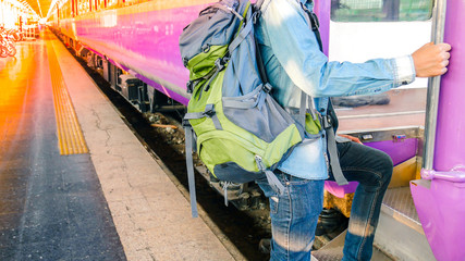 Traveler holding and stepping up to a train with backpack for journey travel at train station. Travel concept.