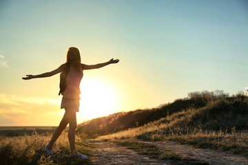 Silhouette of woman on sunset sky background