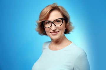 Portrait of beautiful middle-aged woman with eyeglasses on blue background