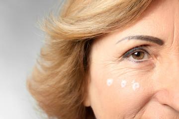 Gorgeous senior woman with anti-aging facial cream, closeup