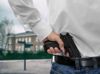 Man with gun on school background