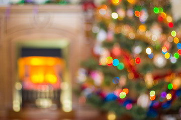 Blurred Christmas background with a fireplace and a Christmas tree.