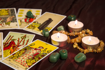 Tarot cards with runes and burning candle