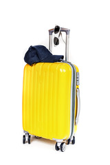 Travel yellow bag with cap and sunglasses on white background.
