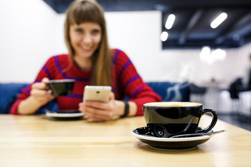 Сup of coffee on the background blurred young girl holding a smartphone and a cup