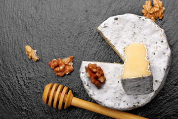 Camembert cheese with nuts and spoon for honey and honey on dark slate background.top view