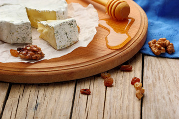 Camembert and brie cheese on wooden background with nuts spices and honey. Italian food. closeup .selective focus